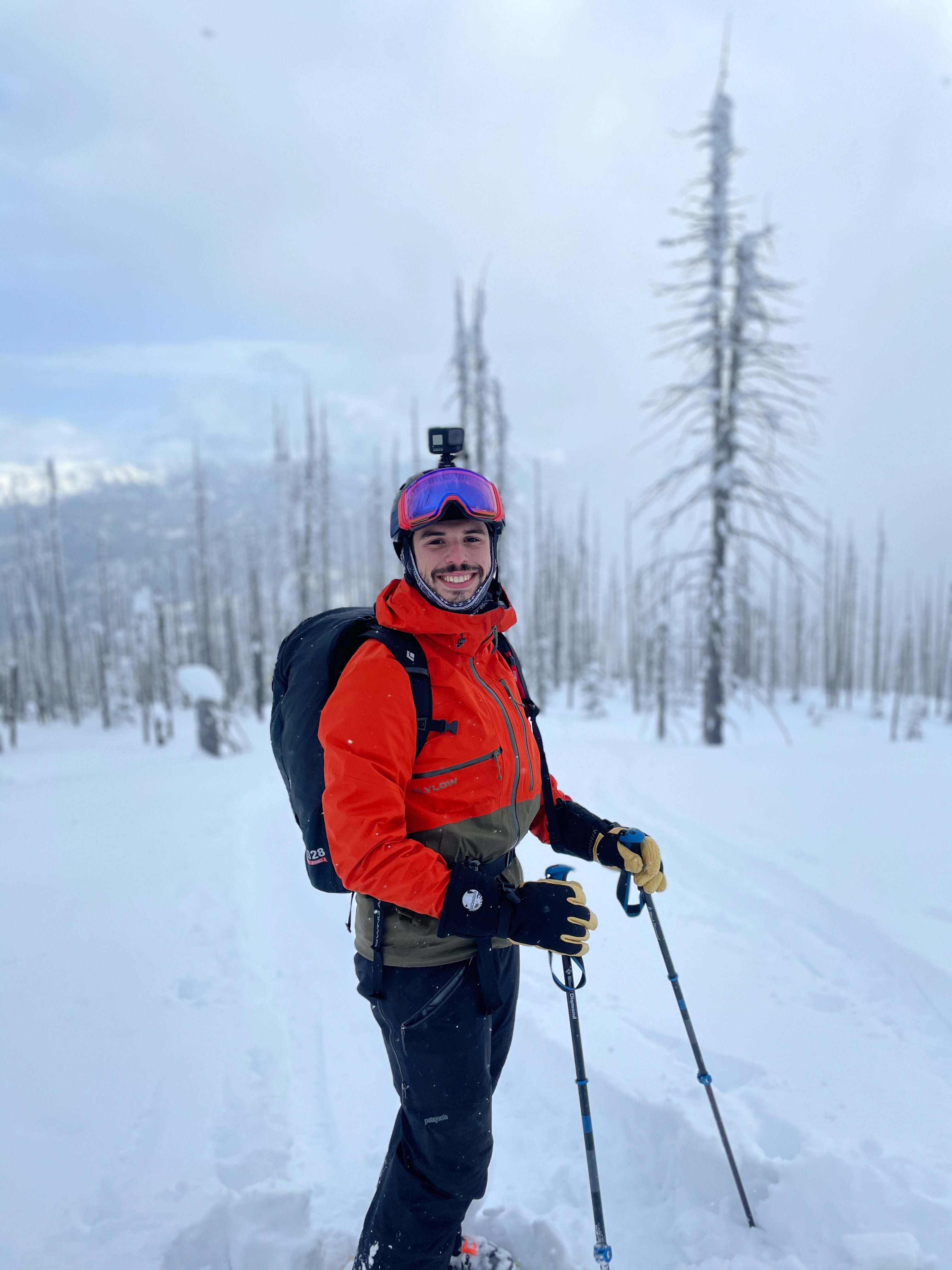 Yours truly, geared up to ski, standing among a field of sparse barren trees and snow